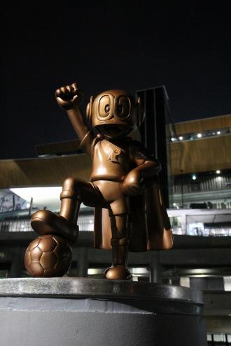 夜のパーマンブロンズ像と、等々力陸上競技場メインスタンド