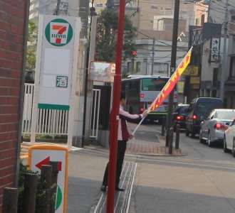 府中街道で旗を振るスタッフ