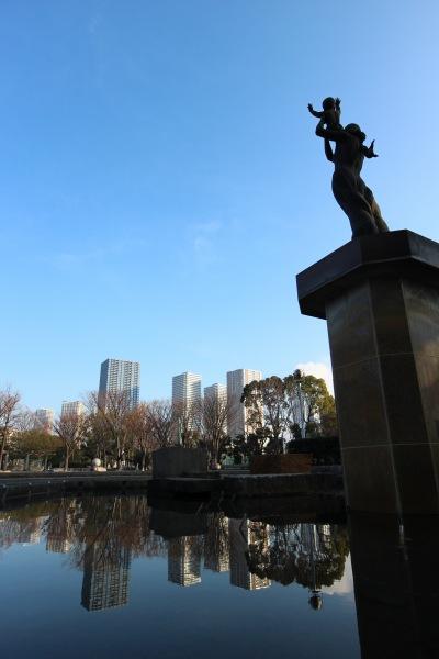 「平和への祈り」像と鏡面世界のタワーマンション