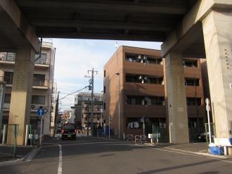 「今井堀踏切」の信号(奥)と保育所建設予定地(右)