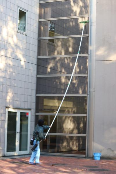 地上から、柄の長いモップで窓掃除